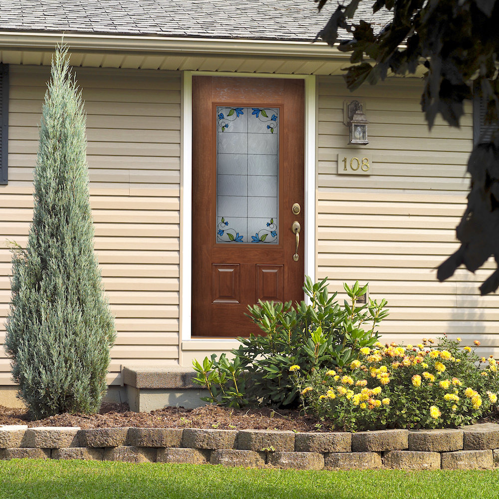 Wood front door with brass hardware and decorative privacy glass on tan house with yellow flowers and bushes in the front.