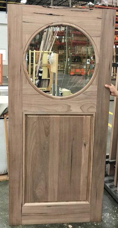 Custom wood door with circle cut in the center with clear glass.