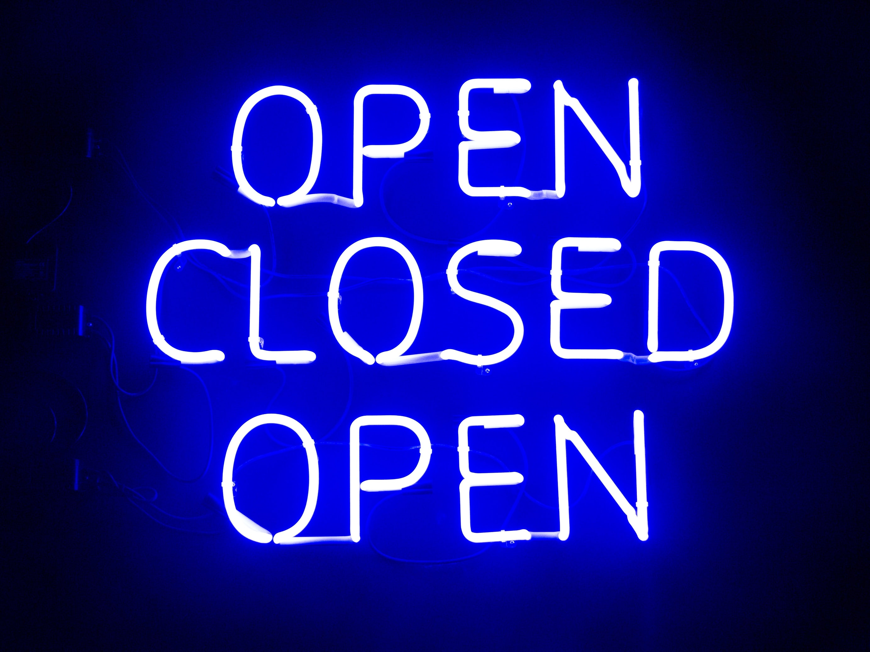 Blue neon sign of the words open closed and open on a black background