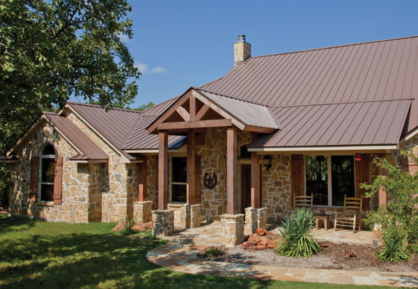 Mueller CF roof in bright copper on a stone home with wood trim.