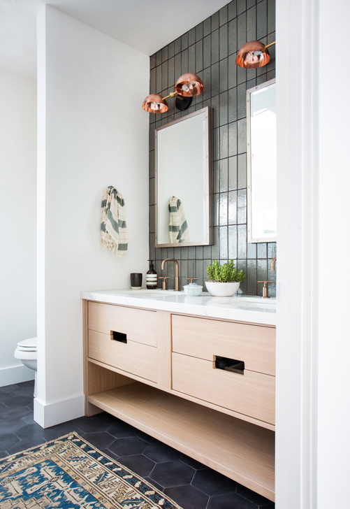 copper bathroom sconces with gold faucets black floor tile and wood vanity