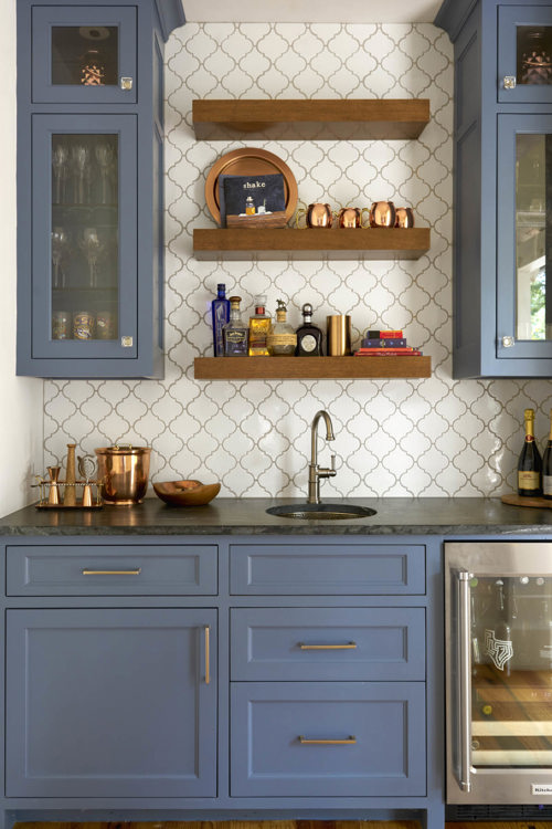 blue cabinets with gold hardware and dark countertop