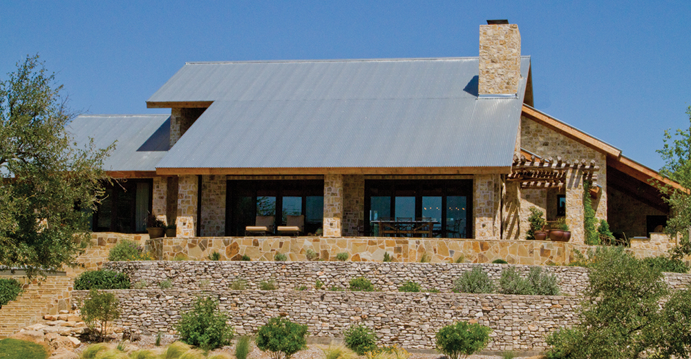 A corrugated metal roof on a stone facade home.