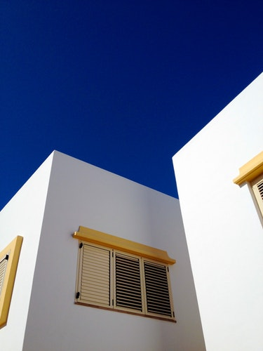 Image of exterior window coverings for additional energy savings. This image shows yellow window shutters on a white building with a dark blue sky.