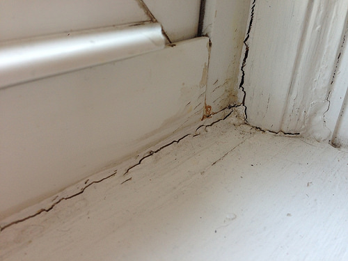 Image of interior  window frame corner with broken or cracked seals.