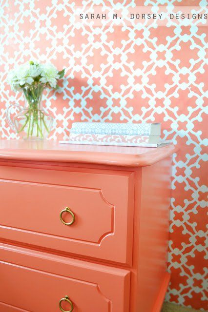 Coral side table with gold ring drawer knobs. The side table is set against a wall featuring coral wallpaper and has flowers as well as books set on top.