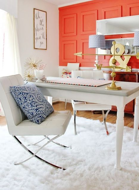 "Image of office space with accent wall painted in coral. On the ground is a fluffy white rug with a wooden white desk and two modern white chairs set on top of the rug. Decor includes a navy blue throw pillow on each chair and a colorful pillow on a chair in the background. Other accessories in the image are gold accent pieces as well as a mirror and a sign that says ""All the places you'll go""."