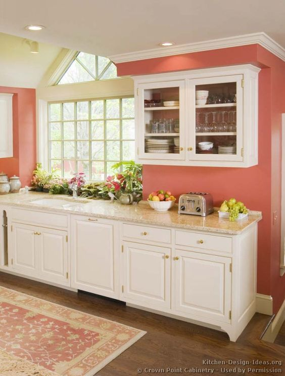 Kitchen featuring white cabinets, stone counters, coral walls, and walnut stained wood floors.