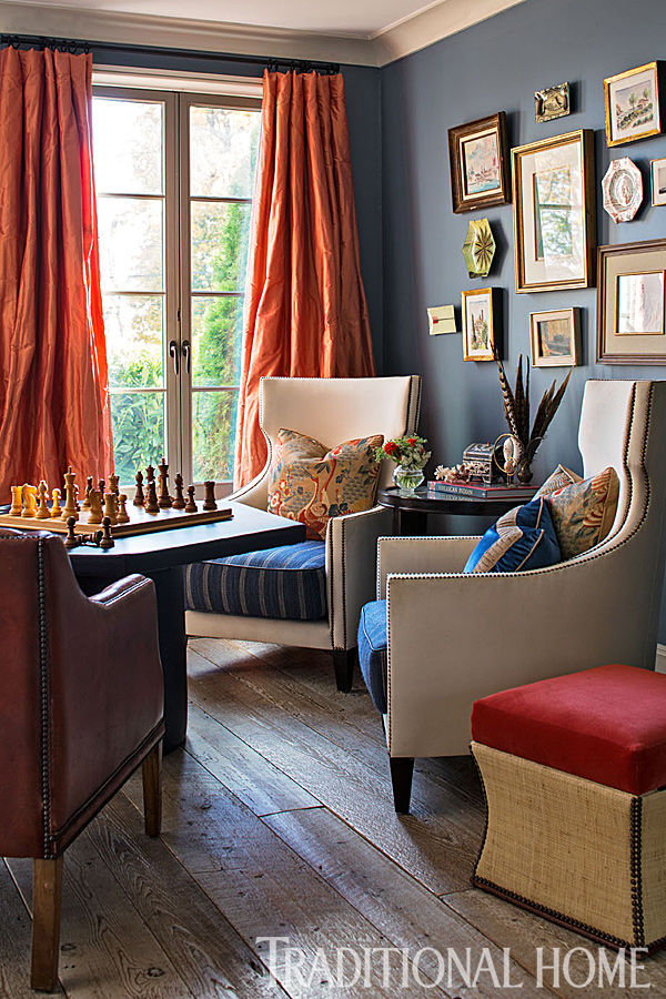 The photo shows an eclectic room with a diverse collection of furniture and decor. The walls in the room are a navy blue, the floors are a weathered oak, the curtains are taffeta fabric in coral.