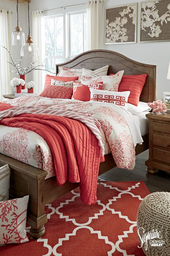 Neutral bedroom color palette with coral accents in the bedding, rug, and decor.