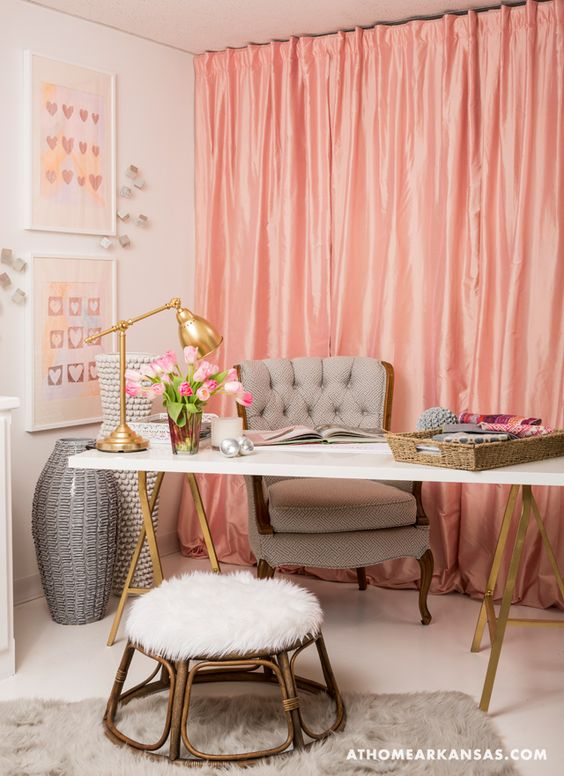 This office space has a youthful and feminine look. It features a coral fabric curtain wall as a backdrop, white walls, a white desk with gold accents, and a gray chair.