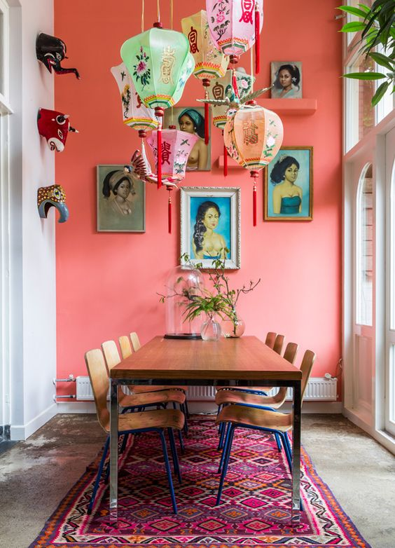 Room with a table that could be a dining room or meeting room. The room has white walls and an accent wall painted in coral. The room features many accessories including a colorful floor rug, hanging lanterns, and wall art.