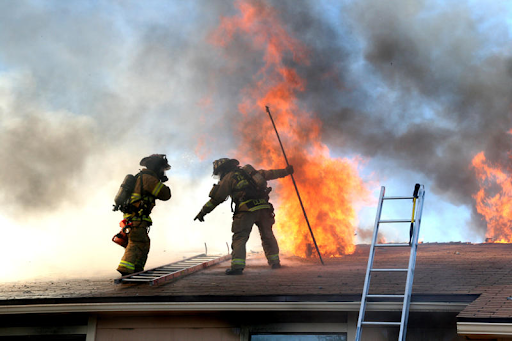 Two firefighters atop a burning residential roof producing large clouds of black smoke.