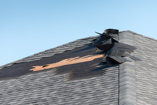 Close up of a roof pitch with several squares of asphalt shingle peeled back from high winds.
