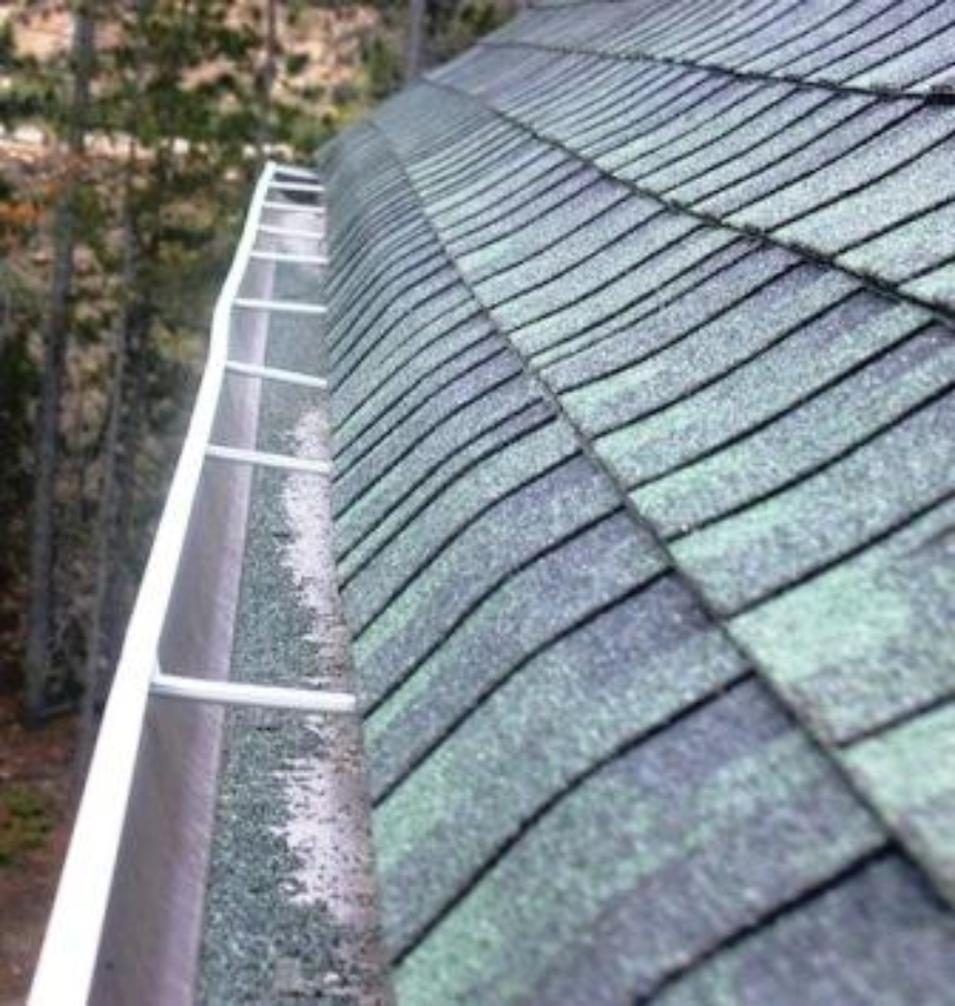 A view of asphalt shingles and a gutter full of asphalt granules that have fallen off of the shingles.