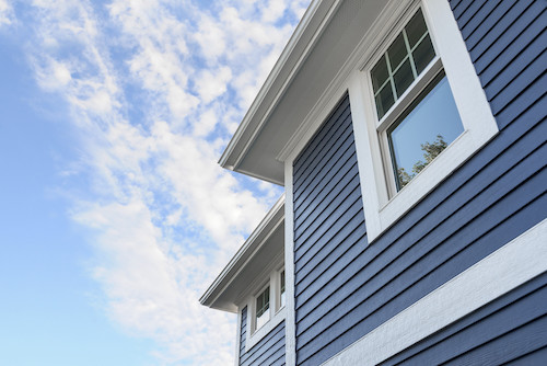 Blue James Hardie lap siding with white trim on a two story house