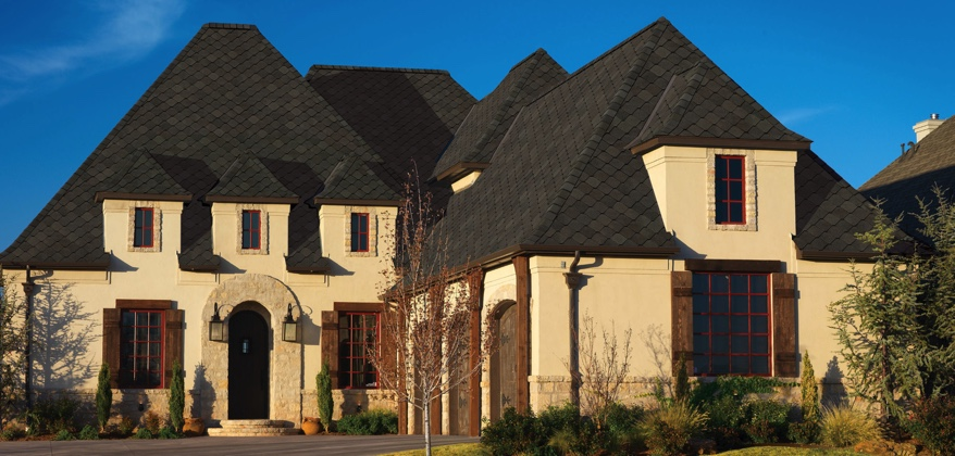 Light colored stuccoed home with wood trim and dark sienna shingles.