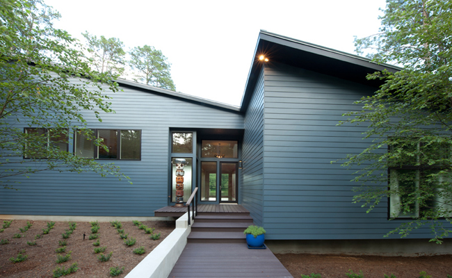 Modern house with sharp lines, navy blue horizontal siding and dark wood walkway