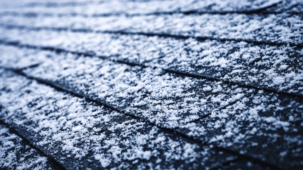 A light dusting of snow atop dark colored asphalt roof shingles.